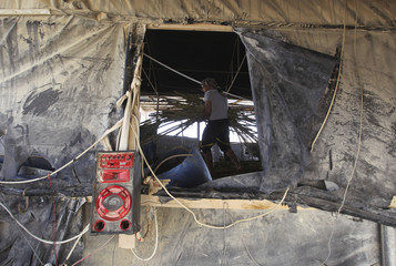 A tunnel worker carries wood as he repairs a smuggling tunnel on the border between Egypt and the southern Gaza Strip