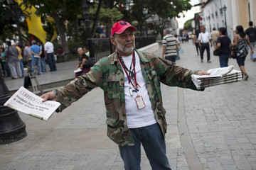 A supporter of Venezuelan President Chavez sells a newspaper with information about president's health in Caracas