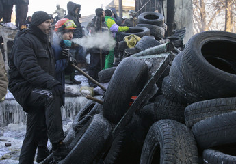Anti-government protesters stand next to a barricade at the site of clashes with riot police in Kiev