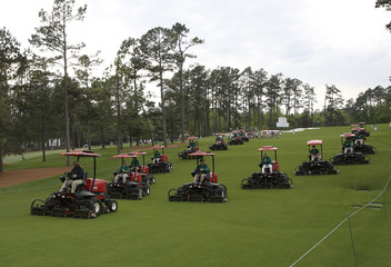 Grounds keepers make their way up the seventh fairway in their mowers during a players practice round ahead of the 2015 Masters at the Augusta National Golf Course in Augusta