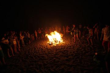 People gather around a bonfire on a beach on San Juan's night in Malaga