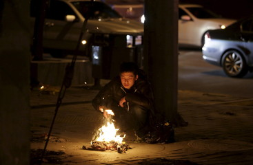 Resident burns joss paper money on the Tomb-Sweeping Day in Beijing