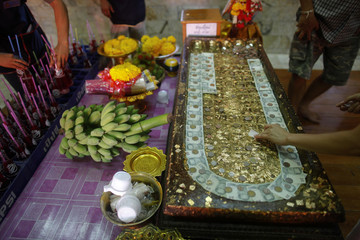 People pray in front of the Red Lips shrine at Wat Prommanee temple in Nakhon Nayok province where people lie in coffins during a religious ritual