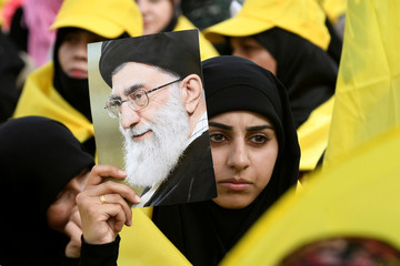 A woman carries a picture of Iran's Supreme Leade Khamenei as she watches Lebanon's Hezbollah leader Nasrallah appear on a screen during a live broadcast to speak to his supporters at an event marking Resistance and Liberation Day in the Bekaa Valley