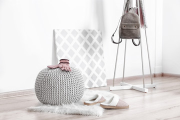 Knitted pouf with clothes in modern hall interior