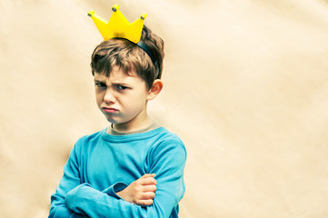 Angry boy with a crown on his head on a light background