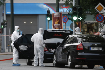 Forensics officers inspect the car of former Greek prime minister and former central bank chief Lucas Papademos following the detonation of an envelope injuring him and his driver, in Athens