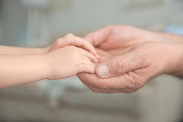 Senior man and little child holding hands, closeup