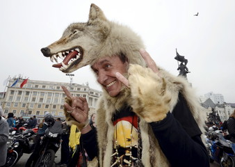A participant wearing a wolf skin poses for a picture as he attends a gathering to celebrate the opening of a new bikers' season in the Russian far eastern city of Vladivostok