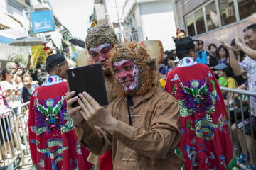 A man playing the role of the Monkey King takes photos with his phone during a Bun Festival parade at Hong Kong's Cheung Chau island
