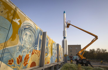 Workers renovate a model of a Proton booster rocket at Baikonur cosmodrome