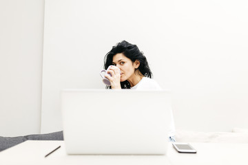 Woman working with her laptop while drinking coffee