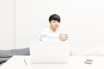 Asian man working with his laptop while drinking coffee