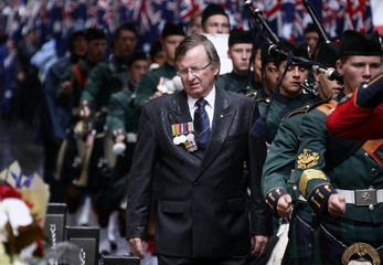 A man wearing service medals looks at the Cenotaph as he walks in the annual ANZAC Day march through central Sydney