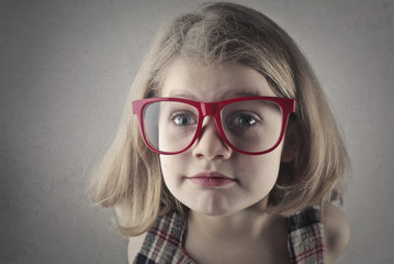 Blonde child with big red glasses