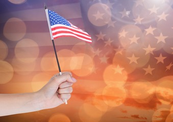 Hand holding American flag with sparkling light bokeh background