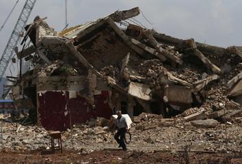 Worker walks past a demolition site in Kunming