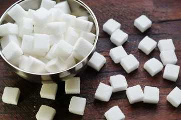 White sugar cubes  on wooden background