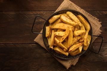 Crunchy roasted potatoes in skillet on dark rustic texture