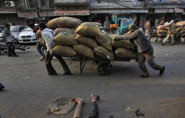 Labourers, with a cart loaded with sacks of spices, walk past a man lying on road at a wholesale grocery market in the old quarters of Delhi