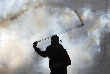 A Palestinian protester uses a slingshot to throw back a tear gas canister fired by Israeli troops during clashes, following the funeral of Palestinian minister Ziad Abu Ein near Ramallah