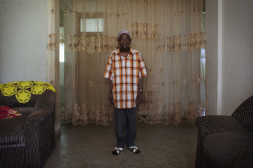 Former independence fighter Bangura poses for a picture in the living room of his house in the capital Bissau