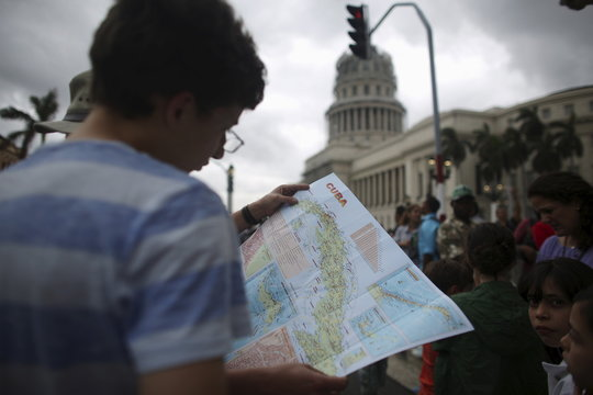 Tourists from Mexico look at a map as people gather for an eventual visit of U.S. President Barack Obama to downtown Havana, Cuba