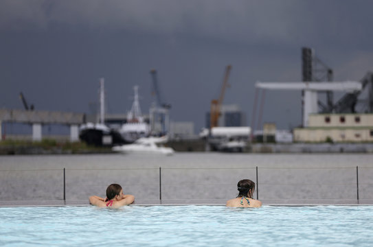"Women look from a floating open-air swimming pool called ""Badboot"" in the port of Antwerp"