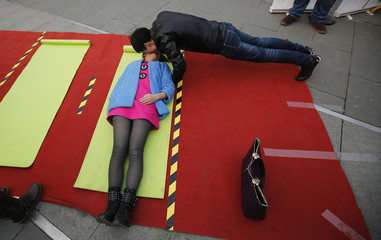 A couple kisses, as the man does push-ups, during a kissing contest held in celebration of Valentine's Day at the Happy Valley amusement park in Beijing