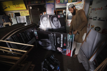A man uses a stapler while he fixes a political campaign poster on to a wooden frame at his workshop in Karachi