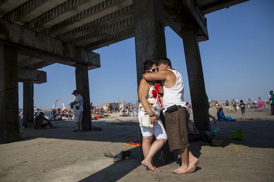 A man and woman kiss under the boardwalk at Coney Island Beach in Brooklyn, New York