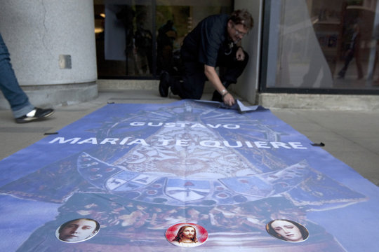 Ricardo Aimare, a fan of Gustavo Cerati, lays a support poster on the floor of La Trinidad hospital where the singer is being treated, in Caracas