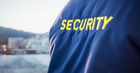 Back of security guard jacket against blurry skyline