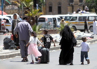 A displaced family with luggage flee from an airstrike on an army weapons depot in Yemen's capital Sanaa