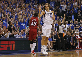 Dallas Mavericks' Dirk Nowitzki (R) celebrates a three point basket in front of Miami Heat's Udonis Haslem during Game 3 of the NBA Finals basketball series in Dallas