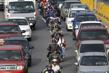 Motorcyclists drive in a line among the traffic during rush hour on a highway in Caracas