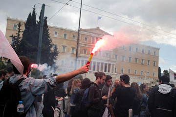 A member of the communist-affiliated PAME union lights a flare, as the parliament building is seen in the background, during a 48-hour general strike against tax and pension reforms in Athens