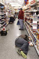 People rest at the aisle of a Publix grocery store after being stranded due to a snow storm in Atlanta
