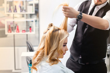 handsome Hairdresser does a hairstyle for a blonde girl in a beauty salon