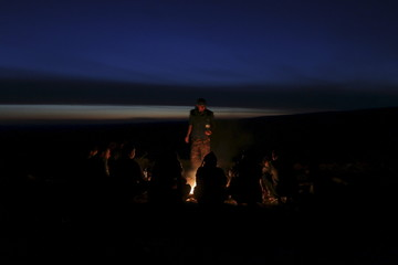 Fighters from the Democratic Forces of Syria warm themselves by a fire at sunset in the southwestern countryside of Hasaka