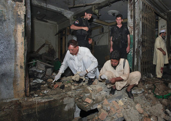 Security officials survey the site of multiple bomb blasts in Peshawar