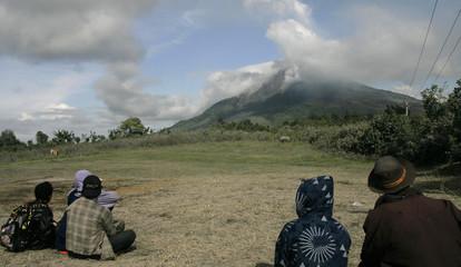 Villagers look toward Mount Sinabung volcano as it spews smoke in Perteguhan village