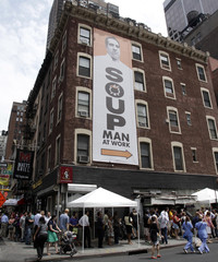People stand in line outside the The Original SoupMan location at 55th street and 8th avenue for its reopening in New York