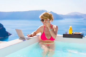 Busy business woman working while on vacation in pool