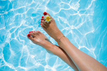 Woman's legs over the swimming pool