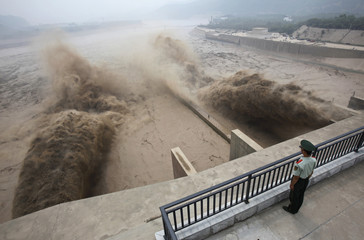 A paramilitary guard watches as sediment-laden flood water gushes through the Xiaolangdi Dam on the Yellow River in Luoyang