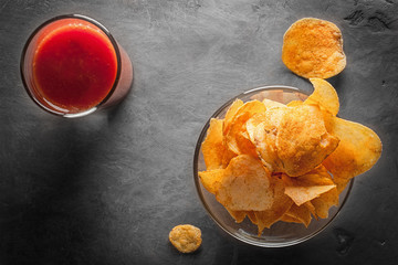 Potato chips in bowl with tomato juice in glass