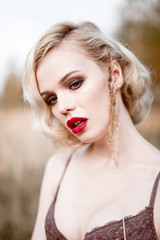 Beautiful and elegant smiling sexy blonde woman with red lips and hair waves wearing beige liingerie posing on the field outdoors summer, retro vintage style and fashion.