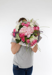 A girl in casual clothing is holding a bouquet of flowers. No face. Unrecognisable