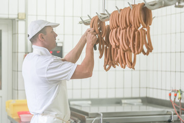 Mann in Fleischerei hängst Würste auf Haken